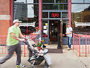 31 MAY 2020 - DES MOINES, IOWA: A man pushes a baby stroller past a shattered restaurant front in Des Moines Sunday morning. A group of rioters, protesting the death of George Floyd in police custody in Minneapolis, smashed windows in businesses and restaurants around the Polk County Courthouse in Des Moines. Des Moines police said they made 25 arrests Saturday night and very early Sunday morning. No one was hurt in the disturbances.    PHOTO BY JACK KURTZ