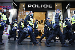 © Licensed to London News Pictures. 19/12/2020. London, UK. Police pass a branch of the retailer POLICE during an anti-lockdown protest in Oxford Street in central London. Hundreds of police, some in riot gear, have started to arrest demonstrators. Photo credit: Peter Macdiarmid/LNP