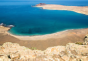 View over El Rio channel to the southern tip of Graciosa Island with sandy beach on  Lanzarote in foreground,, Canary Islands, Spain