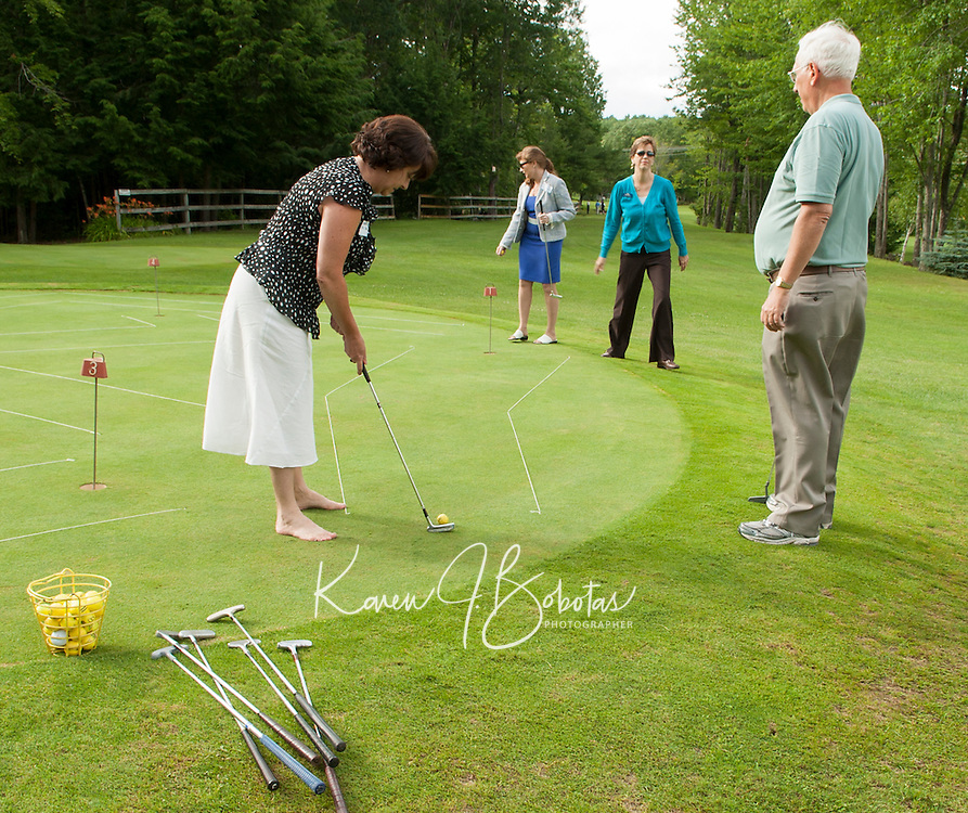 Debbie Bolduc, Ginger Dubois and Karen Hickey practice some unconventional putting skills set up for them during the Business After Hours gathering at Bolduc Park Wednesday evening.  (Karen Bobotas/for the Laconia Daily Sun)