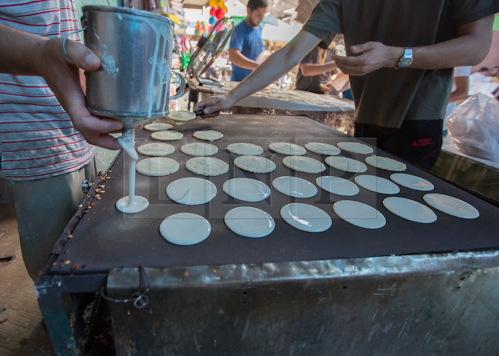 © Licensed to London News Pictures. 17/07/2014. Gaza.   A street seller in Zawya market sells and makes traditional sweets on the tenth day of the war between Hamas and Israel as a 5 hour cease fire is agreed.   Photo credit : Alison Baskerville/LNP