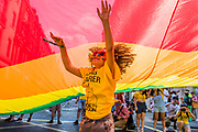 A young flag bearer under the giant pride flag - The London Pride parade and event in Trafalgar Square.