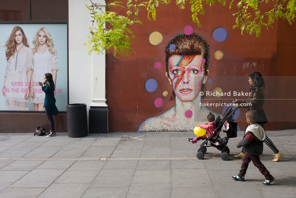 A mother and children walk past the new mural of iconic musician and singer David Bowie has appeared on the wall of Morleys department store in Brixton, Lambeth, south London. The Bowie face is sourced (by artist James Cochran, aka Jimmy C) from the cover of his 1973 album Aladdin Sane at the height of his 1970s fame. The pop icon lived at 40 Stansfield Road, Brixton, from his birth in 1947 until 1953. This cover appeared in Rolling Stone's list of the 500 greatest albums of all time, making #277.