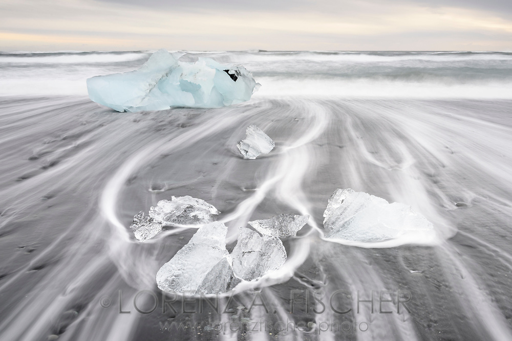 Ice and surf in a long time exposure on the beach of Joekulsarlon on a cloudy but windless morning in wintertime, Iceland