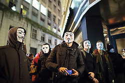 © Licensed to London News Pictures . 05/11/2015 . Manchester , UK . Protesters wearing Guy Fawkes masks outside a branch of Starbucks in Piccadilly Gardens at an Anonymous demonstration in Manchester , UK , this evening (5th November 2015) . Photo credit : Joel Goodman/LNP