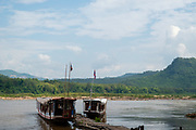 Image of ferry boats docked on the Mekong River at the famous Pak Ou Caves, Laos.