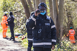 A National Eviction Team enforcement agent working on behalf of HS2 Ltd uses a video camera to film a press photographer during tree felling alongside the Grand Union Canal in Denham Country Park for electricity pylon relocation works connected to the HS2 high-speed rail link  on 6th April 2021 in Denham, United Kingdom. Large swathes of the Colne Valley have been cleared of trees and vegetation for HS2 works which will include the construction of a Colne Valley Viaduct across lakes and waterways.