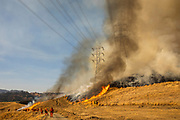 HEALDSBURG, CA - OCTOBER 26: A back fire set by fire fighters burns a hillside near PG&E power lines during firefighting operations to battle the Kincade Fire in Healdsburg, California on October 26, 2019.