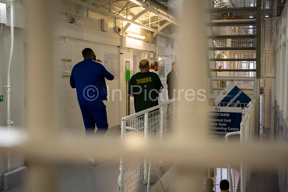 Two male prisoners walk down the landing towards to Prison Officers in G Wing Level 2 of Her Majesty's Prison Pentonville, London, United Kingdom.