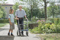Boy helping grandfather with mobility walker at rest home park, Bavaria, Germany