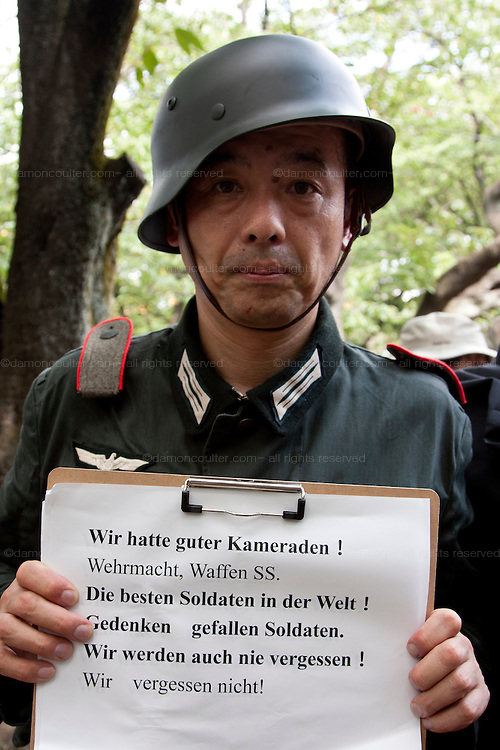 A right winger in nazi uniform holds a sign proclaiming brotherhood with the Wehrmacht and Waffen SS soldiers at the commemorations of the end of the Pacific War on August 15th at Tokyo controversial yasukuni shrine. Tokyo, Japan, Monday August 15th 2011