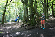 A father pushes his young son on a woodland swing in Ecclesall Woods, on 29th June 2019, in Sheffield, England.