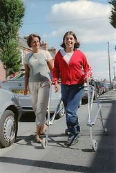 Girl with Cerebral Palsy using frame to walk along pavement with mother,