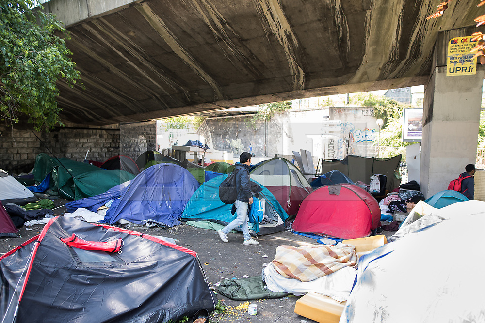 © Licensed to London News Pictures . 09/05/2017. Paris, France . A man walks between tents at the scene where French police have cleared approximately 1000 people from an ad hoc roadside camp under roadways along a central reservation , in which migrants were living , in Porte de la Chapelle in North Paris , this morning (9th May 2017) . Photo credit: Joel Goodman/LNP