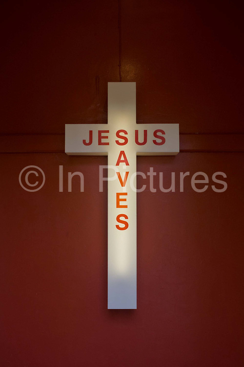 A Jesus Saves neon sign in the entrance of an evangelical church in Peckham, south London. Inside are the voices and cries of the faithful, gathered on Easter Sunday, an important date in the Christian calendar. The cross is mounted on the inside wall, illuminated by its neon tube inside the plastic outer casing.