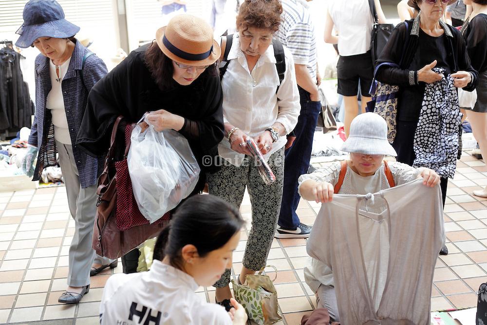 senior women shopping for secondhand clothing at an outdoors fleemarket Japan