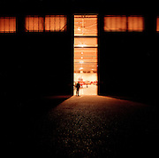 A lone figure stands silhouetted against a hangar belonging to the elite 'Red Arrows', Britain's prestigious Royal Air Force aerobatic team at RAF Scampton, Lincolnshire. Two huge hangar doors are ajar revealing an orange glow spilling on to the concrete outside. A Hawk jet aircraft is parked awaiting overnight maintenance. Engineers talk inside as the door travels along its track. The men are the team's support ground crew and eleven trades are imported from some sixty that the RAF qualifies. The hangar dates to World War 2, housing Lancaster bombers of 617 Dambusters squadron who attacked the damns of the German Ruhr valley on 16th May 1943 using the Bouncing Bomb. This version of BAE Systems Hawks are low-tech, without computers nor fly-by-wire technology, Some of the  team's aircraft are 25 years old and their airframes require frequent overhauls due.