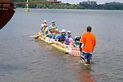 Family in large canoe made from milk cartons finish race on Lake Calhoun. Aquatennial Beach Bash Minneapolis Minnesota USA