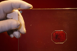 © Licensed to London News Pictures. 02/06/2014. LONDON, UK. An employee of Sotheby's auction house holds a case containing the sole-surviving 'British Guiana One-Cent Magenta' stamp dating from 1856, on June 2, 2014 in central London. The unique stamp is expected to fetch 10 to 20 million USD (£6-12m) when auctioned in New York, USA on June 17, 2014. The stamp was initially discovered in 1873 by a 12-year old Scottish boy living in British Guiana, South America who sold it to a local stamp collector for several shillings. Photo credit : Tolga Akmen/LNP