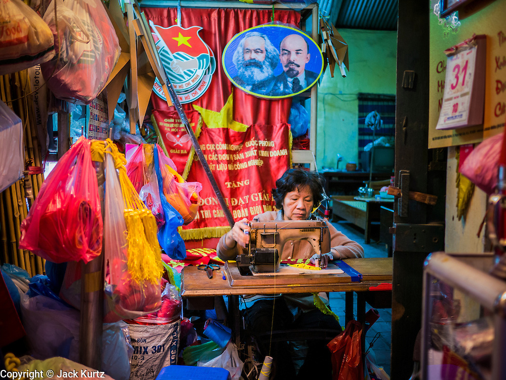 31 MARCH 2012 - HANOI, VIETNAM:   A woman works on revolutionary banners under a portrait of Marx and Lenin in her shop in the Old Quarter of Hanoi, Vietnam.   PHOTO BY JACK KURTZ