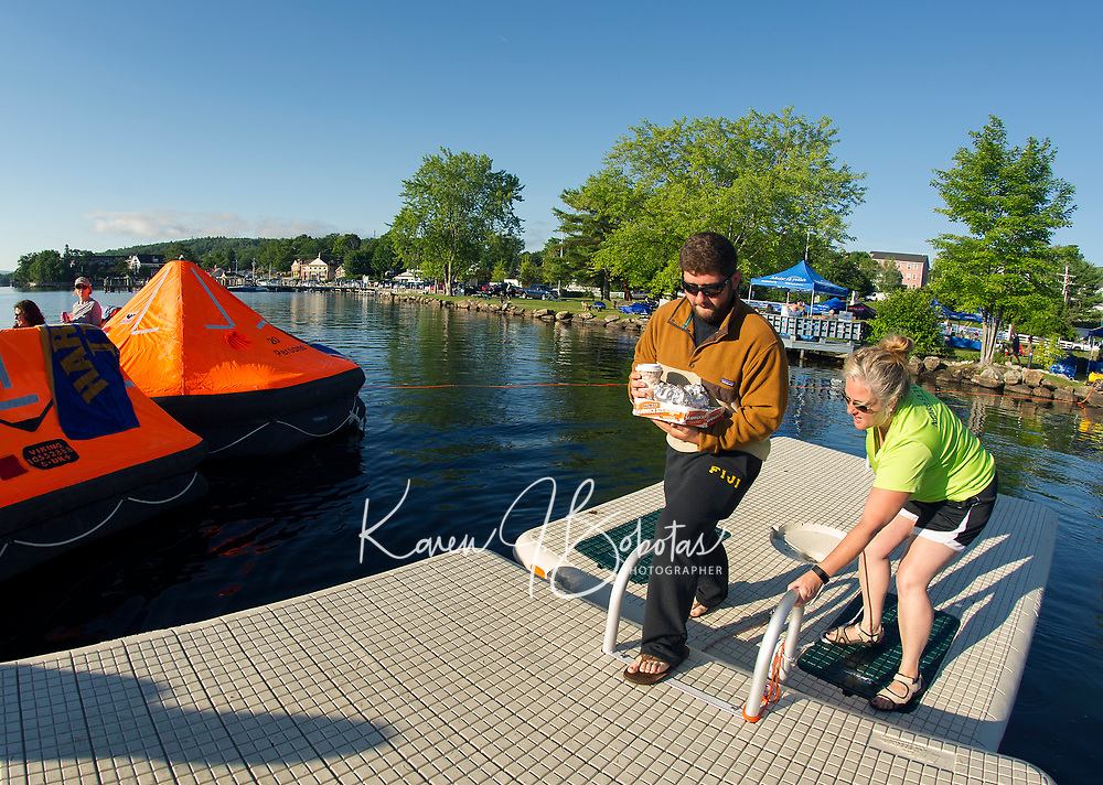 Lucas Gagne and Wanda Keenan bring out coffee and breakfast sandwiches to the overnight rafters early Saturday morning during the Rafting for Wishes event with Make A Wish on Meredith Bay at Hesky Park.  (Karen Bobotas/for the Laconia Daily Sun)