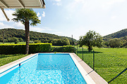 Villa with pool and surrounded by green lawn on a summer day. Nobody inside