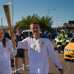 Birkenhead, UK, 1st June, 2012. The Olympic Torch relay arrives in Birkenhead through the Wallasey Tunnel on a route back Liverpool on the Mersey Ferry via Birkenhead Park. Brian Powell, Registered Blind, walks with his daughter.