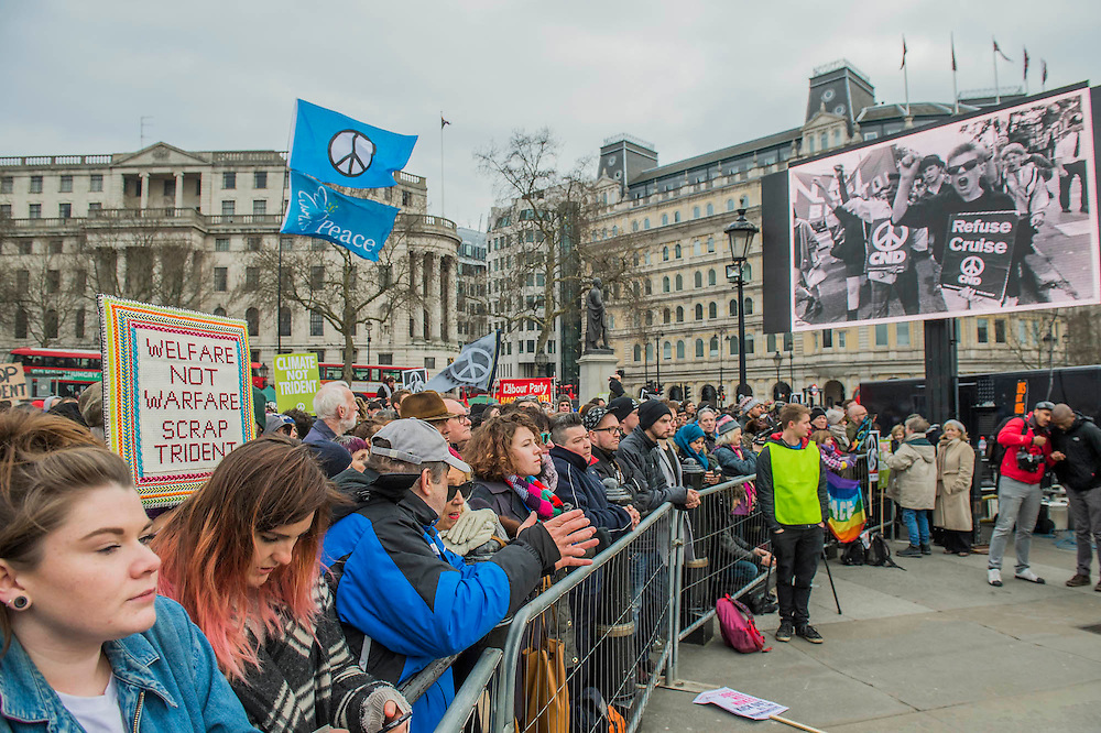 """A big screen shows images from historic marches in Trafalgar Square - A CND led national demonstration to protest against Britain's nuclear weapons system: Trident. They state - """"The majority of the British people, including the Labour leader Jeremy Corbyn, oppose nuclear weapons. They are weapons of mass destruction, they don't keep us safe and they divert resources from essential spending."""" The march from Hyde park to Trafalgar Square was supported by Friends of the Earth, the Green party, Greenpeace, the PCS Union, the Quakers, the Stop the War Coalition, War on Want amongst amny others."""