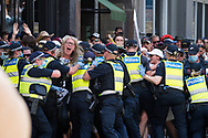 Police scuffle with protesters on the street near the state parliament as they force the police line. The groups who have organised the many Freedom Day protest over the last 3 months, attempted to march to State Parliament on Melbourne Cup Day demanding the sacking of Premier Daniel Andrews for the lockdown and attacks on their civil liberties, where they were met with a heavy police presence.  (Photo by Michael Currie/Speed Media)