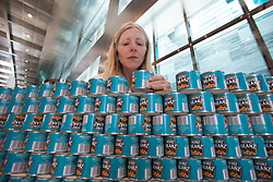 © licensed to London News Pictures. London, UK 24/06/2012. Fiona Dunn carefully positioning a can to a wall of Heinz Beans, which has 3,444 cans. Teams of leading architects, designers and engineers competing today as they sculptures from cans of food at One Canada Square Shopping Centre today. Photo credit: Tolga Akmen/LNP