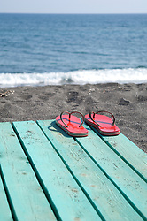 red flip flops on a wooden boardwalk by the sea in Greece