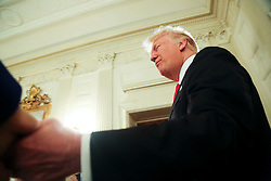 U.S. President Donald Trump shakes hands as he arrives at the National Governors Association meeting in the State Dining Room of the White House, Washington, DC, February 27, 2017. (Pool / Aude Guerrucci)