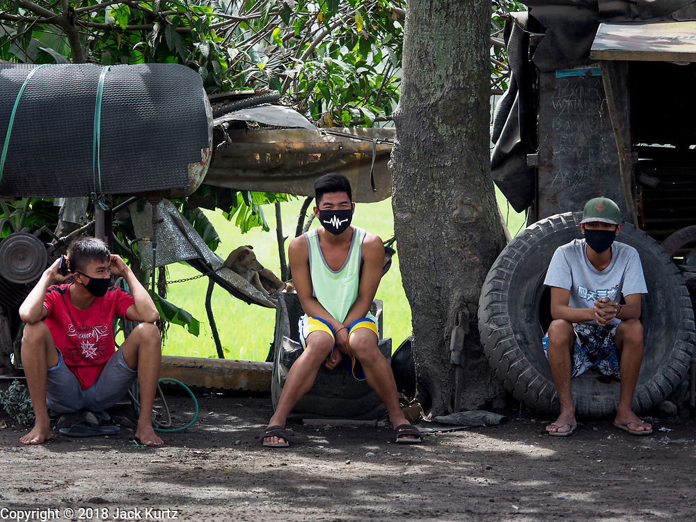30 JANUARY 2018 - GUINOBATAN, ALBAY, PHILIPPINES:  Workers in a car repair shop on the side of the highway in Guinobatan wear face masks as a protection against volcanic ash fall. The volcano continued to erupt but not as dramatically as it did last week. The small eruptions are still sending ash clouds over communities west of the volcano and the government is encouraging people to stay indoors, wear face masks and avoid strenuous activities when ash is falling.    PHOTO BY JACK KURTZ