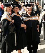 Three mature women pose, University graduation degree award ceremony, St Andrews Hall, Norwich, England