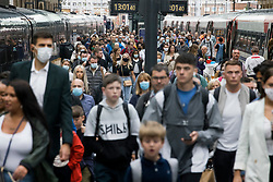© Licensed to London News Pictures. 31/07/2021. London, UK. Members of the public, many not wearing face masks, disembark a train at Kings Cross Station in central London. The UK's COVID-19 cases continue to fall following the removal of restrictions on July 19th. Photo credit: Ben Cawthra/LNP
