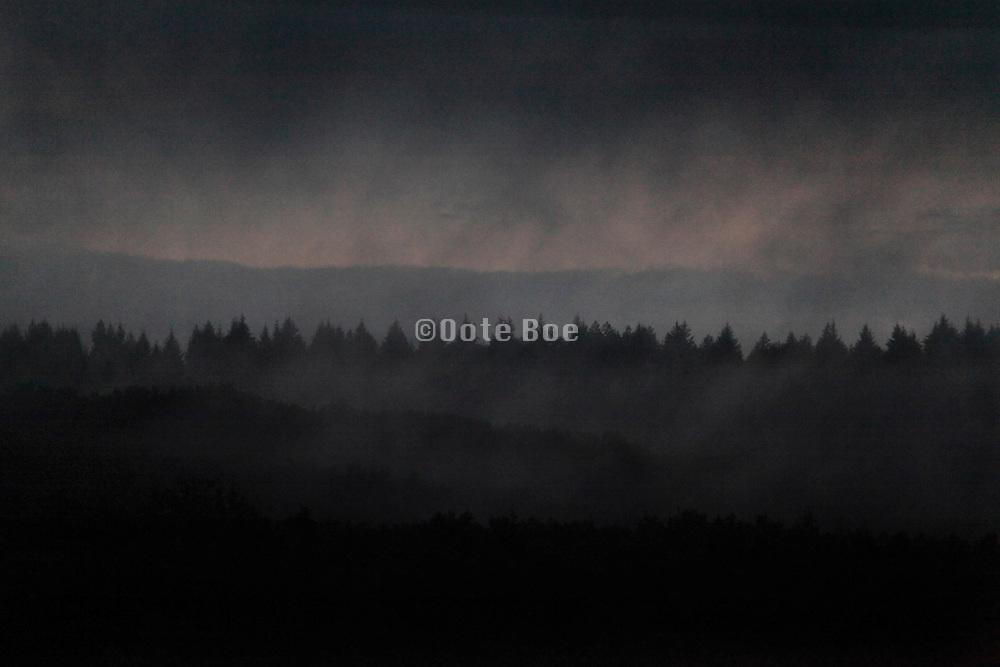 dark setting clouds over wooded rural landscape