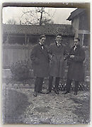 three young adult men standing in backyard