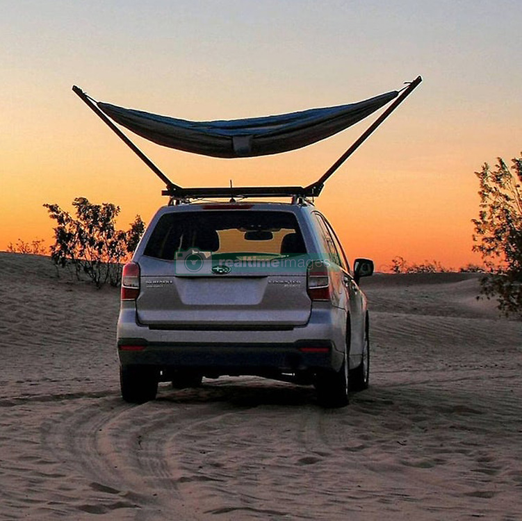 """June 6, 2017 - inconnu - A hammock that can be mounted on a car roof is set to make exploring a more comfortable experience. The US-designed TrailNest collapsible roof-top stand lets a hammock be used just about anywhere.The main reason is sometimes there are no trees – such as in desserts, grassy plains or snowfields.The stand gives adventurers somewhere to hitch their hammock and also provides an elevated view of the surrounding area.The stands attach to car roof bars and each stands holds up to 250 pounds in weight / just over 113 kilos.Inventor Chris Blackthorn said he got the idea after taking his hammock for a drive through the Mojave dessert.He explained it is renowned for beautiful desert vistas but not for an abundance of trees. He added:""""Searching the desert, I finally found a withered trunk with just enough tenacity to suspend one end of my hammock while the other hung from my roof rack. """"The view of the cloudless, starlit sky was beautiful, even if the location near my lone tree was otherwise less than ideal. """"My peaceful solitude was not to last, however, as shortly after dozing off I was awakened by an inquisitive band of coyotes who were persistent enough to return repeatedly throughout the night.""""Upon returning home I began to look at roof top tents, hoping to gain some separation above curious wildlife. """"The idea of a tent on the warm summer nights didn't sound much better than my sleeping platform, though.""""I decided that some experiments were in order, and began the design and construction of the hammock stand.""""I am finally ready to share with everyone the joy that my hammock stand has added to my overland journeys. """"Pulling into camp each night, I finally feel an excitement that was previously lacking, and I can't wait to stretch out each night in a spacious hammock. """"The rooftop vantage elevates me above my surroundings and I fall asleep to views that I will remember for decades"""
