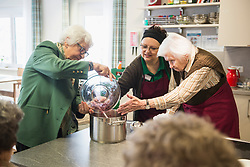 Nursing staff assisting seniors cooking in rest home