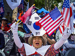 June 16, 2018 - Seoul, Gyeonggi, South Korea - A South Korean woman holding South Korean and American flags cheers during a protest against South Korean President. The protesters allege that Moon is too soft on North Korea and can't be trusted to negotiate with North Korean leader but support US President's efforts to negotiate with North Korea. (Credit Image: © Jack Kurtz via ZUMA Wire)