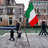 VENICE, ITALY - MARCH 16: Passers by walk in front of an Italian national flag that is displayed ahead of the celebrations for the 150th anniversary of Italy's unification on March 16, 2011 in Venice, Italy. March 17th has been declared National Festivity and events to celebrate the 150th anniversary will run in several Italian cities until the end of the year.