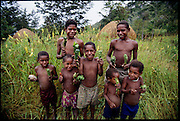 """Dani children show their """"bug packages"""", a collection of twenty or so stink bugs wrapped in leaves to be roasted over a fire and eaten as a tasty protein snack, Soroba, Baliem Valley, Irian Jaya, Indonesia.   (pages 80, 81) ."""