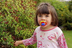 Young girl with autism standing outside in garden sucking on dummy,