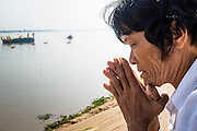 """05 FEBRUARY 2013 - PHNOM PENH, CAMBODIA: A Cambodian woman prays as the Royal Barge carrying the ashes of King-Father Norodom Sihanouk heads up the Mekong River to scatter the revered King's ashes. Sihanouk's ashes will be scattered in locations across Cambodia. Tuesday, they were scattered on the Mekong River. Norodom Sihanouk (31 October 1922- 15 October 2012) was the King of Cambodia from 1941 to 1955 and again from 1993 to 2004. He was the effective ruler of Cambodia from 1953 to 1970. After his second abdication in 2004, he was given the honorific of """"The King-Father of Cambodia."""" Sihanouk died in Beijing, China, where he was receiving medical care, on Oct. 15, 2012.    PHOTO BY JACK KURTZ"""