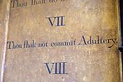 Historic interior of Saint John the Baptist church, Mildenhall, Wiltshire, England, UK 'Thou shalt not commit adultery' commandment
