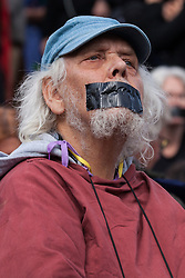 London, UK. 16 October, 2019. A climate activist from Extinction Rebellion with gaffer tape over his mouth defies the Metropolitan Police prohibition on Extinction Rebellion Autumn Uprising protests throughout London under Section 14 of the Public Order Act 1986 by attending a Right to Protest assembly in Trafalgar Square. The Metropolitan Police made arrests, including Green Party co-leader Jonathan Bartley and Guardian journalist George Monbiot, after a group of protesters sat down in the road in Whitehall.
