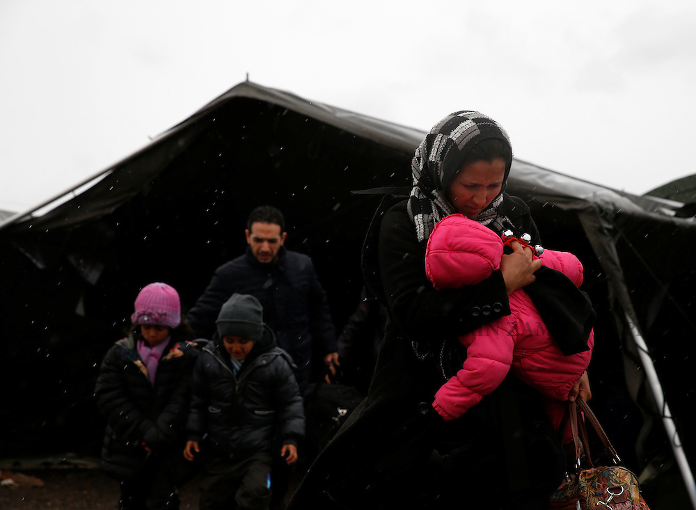 A migrant carries her baby as she makes their way to a tent where aid is distributed as migrants and refugees wait to continue their train journey to western Europe at a refugee transit camp in Slavonski Brod, Croatia, February 10, 2016.<br /> Photo: Darrin Zammit Lupi