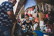 Jayapura, Papua, Indonesia - July 15, 2017: A girl working with family and selling betel nut makes a playful face at the Hamadi market in Jayapura.