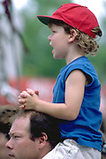 Girl with red cap ridding on dads shoulders age 30 and 3.  St Paul Minnesota USA