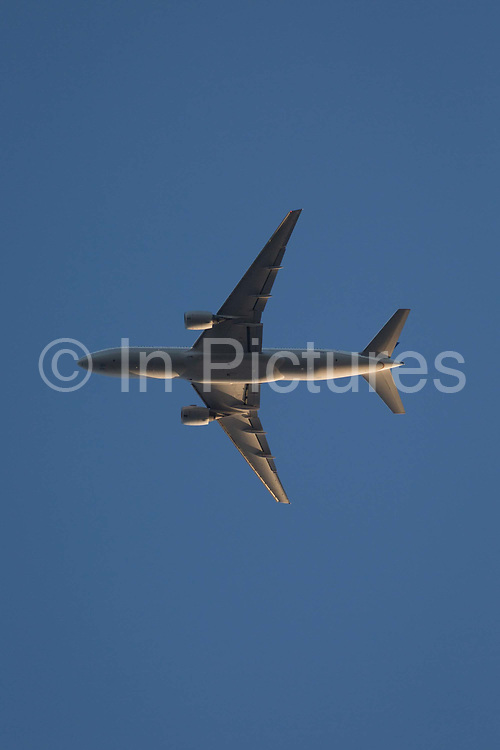 A Boeing 777-222ER jet airliner N228UA flies overhead in blue skies on its flight-path into London Heathrow airport, on 10th August 2018, in London, England.